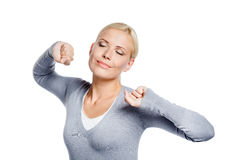 Woman with eyes closed stretches herself Royalty Free Stock Photo