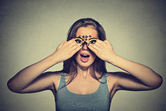 Woman with eyes painted on her hands  on gray wall background Royalty Free Stock Photo
