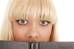 Woman eyes wide over book Stock Photos