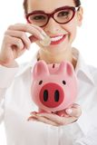 Woman in eyewear putting money to piggybank Stock Images
