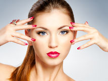 Woman face. Beautiful girl with bright red lips and manicure Stock Image