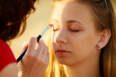 Woman face applying eyeshadow eyes makeup. Stock Photography