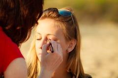 Woman face applying eyeshadow eyes makeup. Stock Images