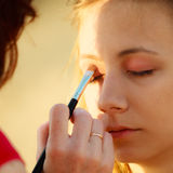 Woman face applying eyeshadow eyes makeup. Royalty Free Stock Photography