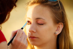 Woman face applying eyeshadow eyes makeup. Stock Image