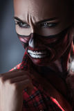 Woman with face art on halloween theme looking away. In studio Royalty Free Stock Photos