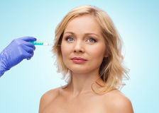 Woman face and beautician hand with syringe Royalty Free Stock Photo