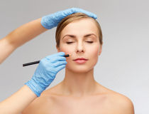 Woman face and beautician hands with pencil Stock Image