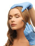 Woman face and beautician hands Stock Images
