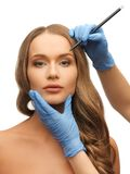 Woman face and beautician hands Royalty Free Stock Photos