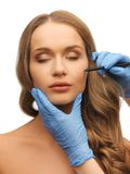 Woman face and beautician hands Royalty Free Stock Photo