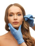 Woman face and beautician hands Royalty Free Stock Photography