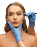 Woman face and beautician hands Royalty Free Stock Images
