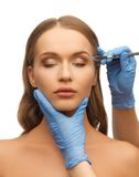 Woman face and beautician hands Stock Photo