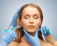 Woman face and beautician hands Stock Photography