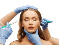Woman face and beautician hands with syringe Royalty Free Stock Photo