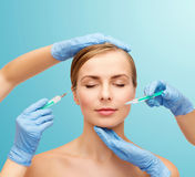 Woman face and beautician hands with syringe Royalty Free Stock Images