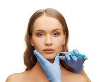 Woman face and beautician hands with syringe Stock Image