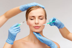 Woman face and beautician hands with syringe Stock Photos