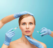 Woman face and beautician hands with syringe Stock Photo