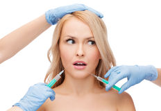 Woman face and beautician hands with syringes Royalty Free Stock Photos