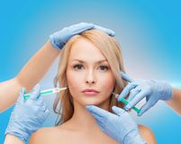 Woman face and beautician hands with syringes Royalty Free Stock Photography