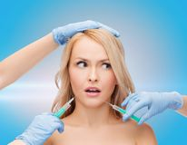 Woman face and beautician hands with syringes Stock Photos