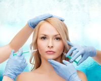 Woman face and beautician hands with syringes Royalty Free Stock Image