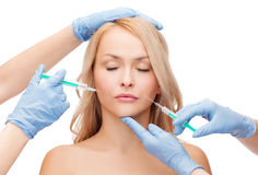 Woman face and beautician hands with syringes Royalty Free Stock Images