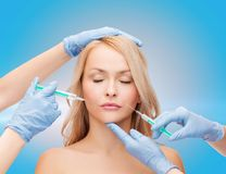 Woman face and beautician hands with syringes Stock Photo