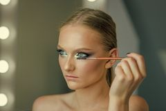 Woman face beauty. Woman use mascara applicator brush, makeup. Woman apply mascara makeup on eyelashes, look. Beauty. Model skin, cosmetics. Girl with young Royalty Free Stock Images