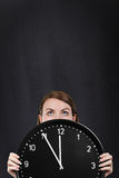 Woman face with a big clock Stock Photo