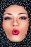 Woman in face with blueberry, berry in the mouth Royalty Free Stock Photo