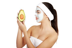 Woman with face clay mask holding avocado Stock Photo