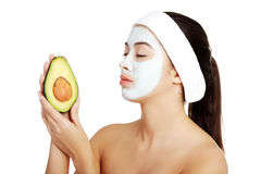 Woman with face clay mask holding avocado. Stock Photo
