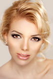 Woman face close up. A pretty young blond trendy. Girl with a be Stock Images