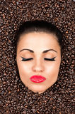 Woman face with closed eyes in the coffee beans Royalty Free Stock Photography