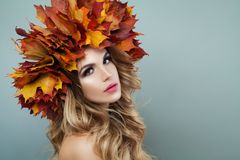 Woman face closeup. Autumn model woman with makeup, blonde hair and fall leaves.  royalty free stock photos