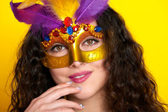 Woman face closeup in carnival masquerade mask with feather, beautiful girl portrait on yellow color background, long curly hair Royalty Free Stock Image