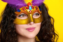 Woman face closeup in carnival masquerade mask with feather, beautiful girl portrait on yellow color background, long curly hair Stock Photo
