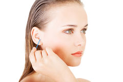 Woman face closeup while cleaning up an ear with a swab Royalty Free Stock Photos