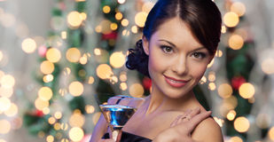 Woman face with cocktail over christmas lights Stock Photos