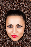 Woman face in the coffee beans Royalty Free Stock Photo