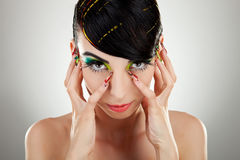 Woman face with color makeup and manicure Stock Photos