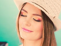 Woman face colorful eyes makeup, summer straw hat stock image