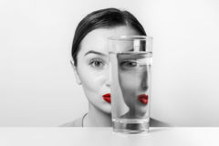 Woman Face Distortion In Water Glass. Woman Face Distortion In Glass Of Water Royalty Free Stock Photo