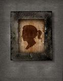 Woman face in frame. Drawing of a woman face in old-fashioned silhouette style in a frame on grunge background Royalty Free Stock Images