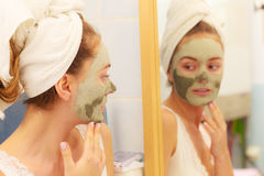 Woman face with green clay mud mask. Skin care. Woman in bathroom with green clay mud mask on face looking at mirror. Girl taking care of oily complexion. Beauty Stock Photos