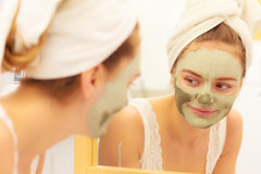 Woman face with green clay mud mask Stock Photos
