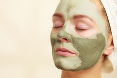 Woman face with green clay mud mask. Skin care. Woman face with green clay mud mask close up. Girl taking care of oily complexion. Beauty treatment Royalty Free Stock Image